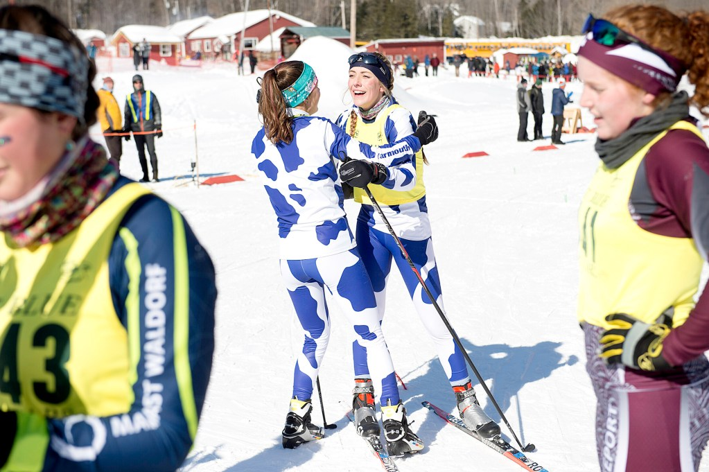 Isabel Brennan, center right, and her Yarmouth  teammate Madeline Marston celebrate after Yarmouth won the Class B state ski championship at Titcomb Mountain in Farmington on Tuesday.