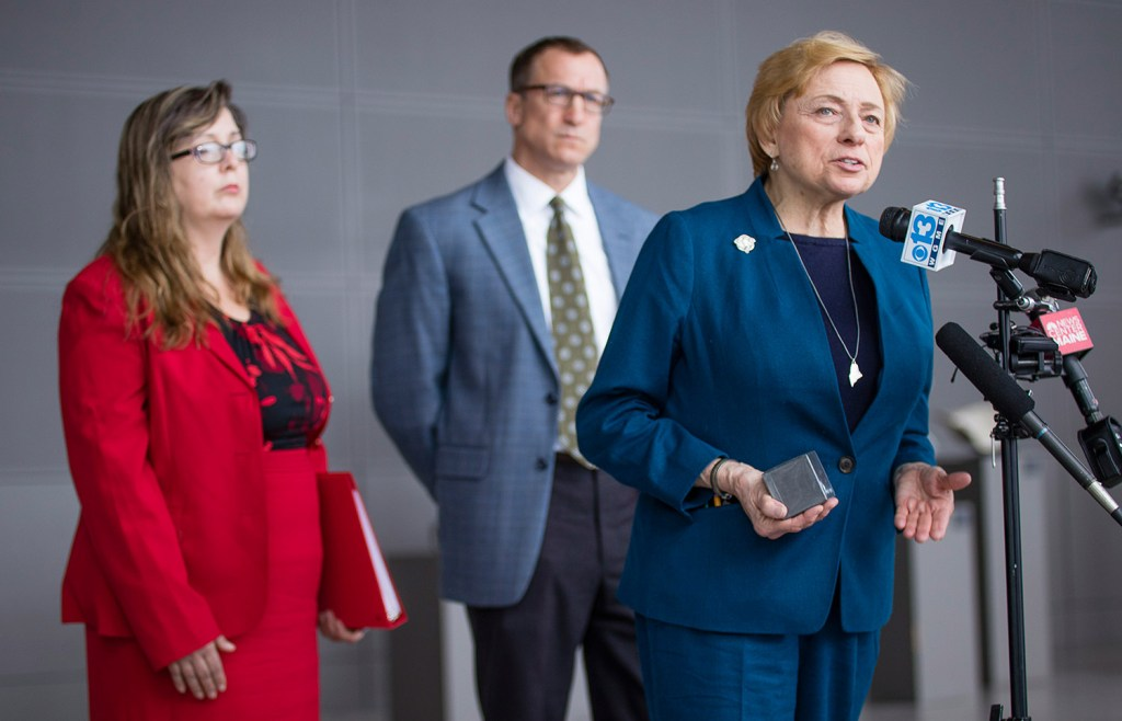 Gov. Janet Mills answers questions during a news conference Thursday at the Portland International Jetport about her support for a plan to build an electric transmission line from Quebec through Maine to Massachusetts. Behind her are Angela Monroe, director of the Governor's Energy Office, and Greg Cunningham, vice president and director of Clean Energy Climate Change for the Conservation Law Foundation Maine.