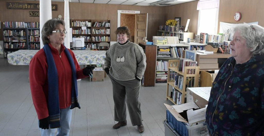 Staff photo by Andy Molloy Cheryl Joslyn, left, and another library volunteer confer Tuesday in Whitefield's library, located in the former Arlington Grange. The library hopes to acquire the structure to sprovide the library a permanent location.