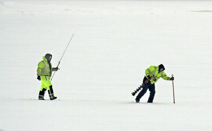 U.S. Geological Service technicians Jason Cyr, right, and Jeremiah Pomerleau pound ice Wednesday on the Kennebec River in Gardiner while collecting samples. The federal agency was collecting data on the thickness of ice from rivers across Maine before a meeting with the Maine Emergency Management Agency on Thursday.