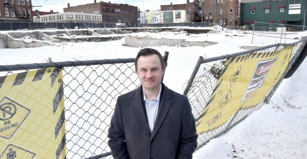 Brian Clark, vice president of planning at Colby College, stands Thursday beside the fenced-in area of the former Camden National Bank and former Levine's building in downtown Waterville that will become the site of a hotel complex.