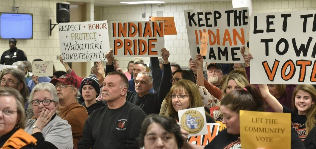 "People for and against the use of the ""Indians"" nickname in SAD 54 schools show signs to school board members during Thursday night's meeting in Skowhegan."