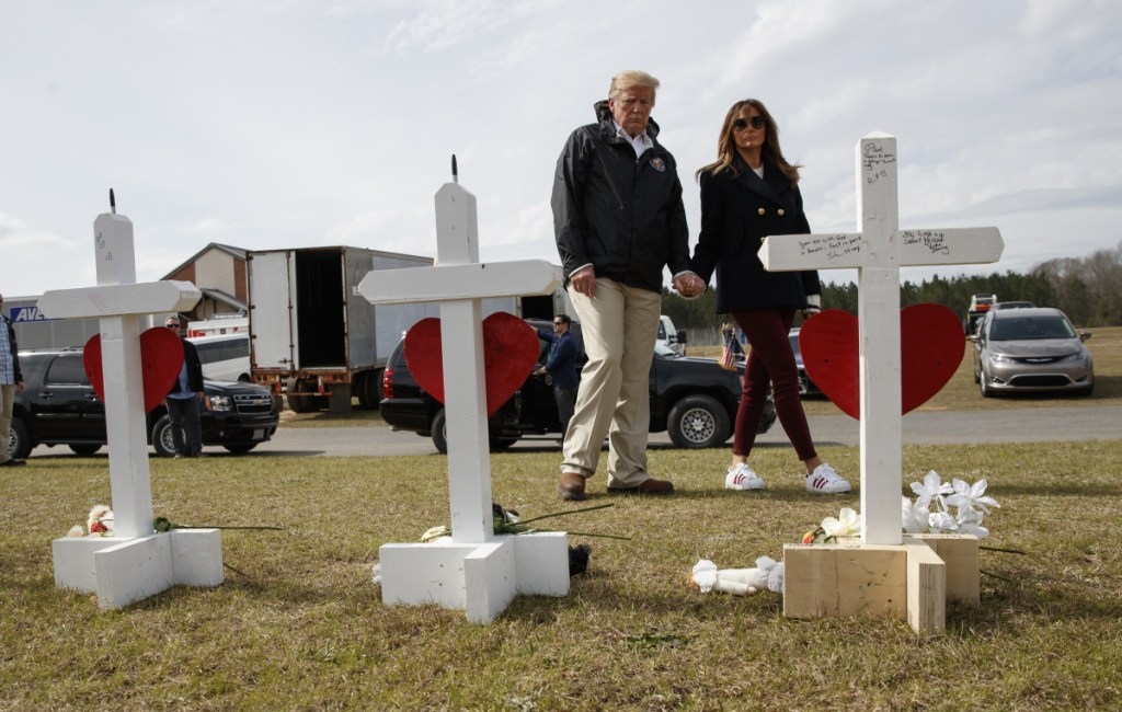 President Trump and first lady Melania Trump view a line of crosses at Providence Baptist Church in Smiths Station, Ala., on Friday as they tour areas where tornadoes killed 23 people last weekend.