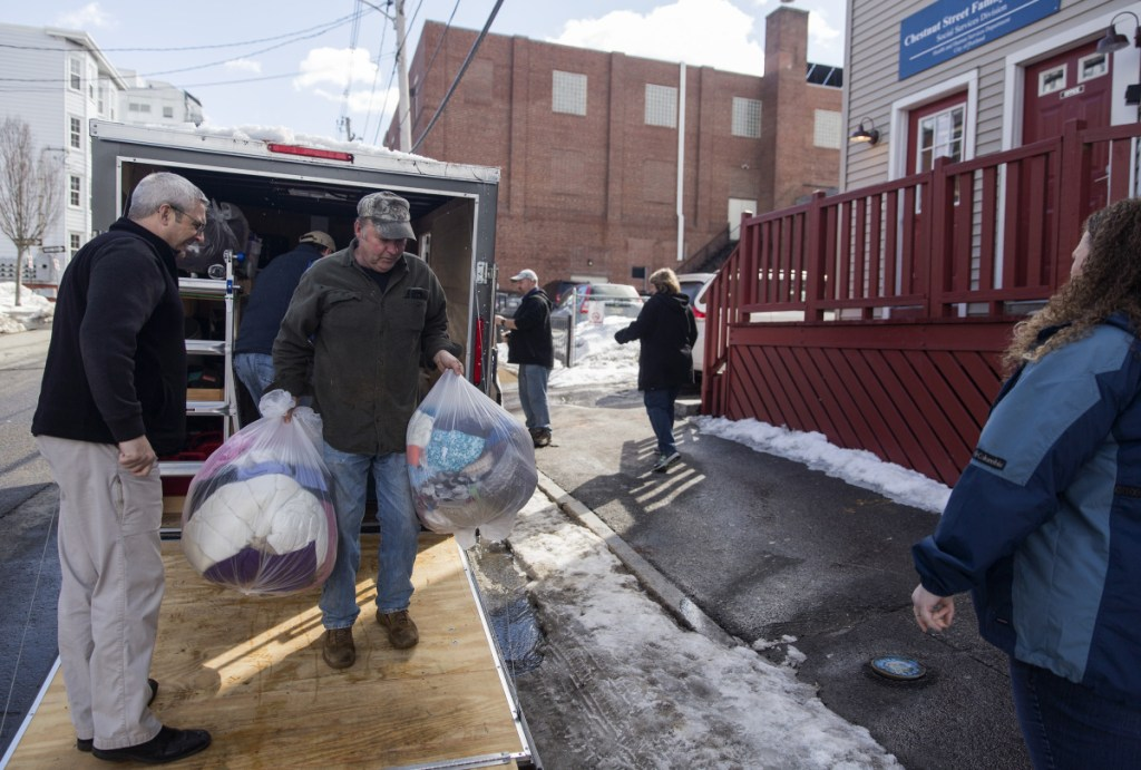 Ron Paquin helps bring winter coats, toiletries and other goods donated by churches in Maine, New Hampshire and Massachusetts into the Portland Family Shelter on Monday.