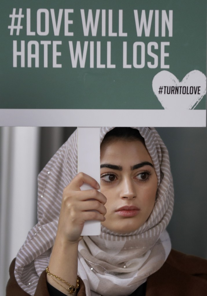"""A demonstrator holds a banner from a multi-faith group, """"Turn to Love,"""" during a vigil at New Zealand House in London on Friday following the deadly attacks on two mosques in Christchurch."""