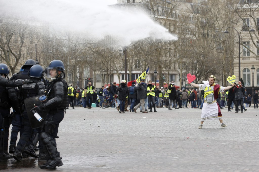 A demonstrator faces police water cannons in Paris. French yellow vest protesters clashed Saturday with riot police near the Arc de Triomphe as they kicked off their 18th straight weekend of demonstrations against President Emmanuel Macron. (AP Photo/Christophe Ena)
