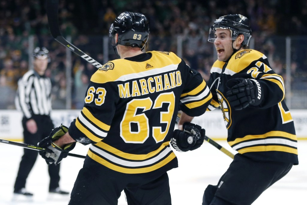 Brad Marchand, left, celebrates with John Moore after scoring in overtime Saturday night to give the Bruins a 2-1 win over the Columbus Blue Jackets.