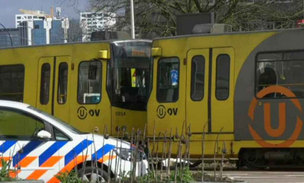 In this image taken from video, a body lies next to a tram as emergency responders attend the scene of a shooting Monday in Utrecht, Netherlands, that killed three people and injured five.
