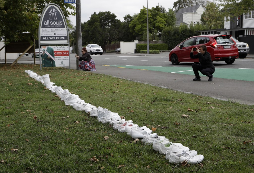 In front of a church Tuesday in Christchurch, New Zealand, people photograph a memorial of 50 pairs of white shoes for the victims of the massacre at two mosques Friday. Four days after the attack, New Zealand's deadliest shooting in modern history, relatives were anxiously waiting for word on when they can bury their loved ones.