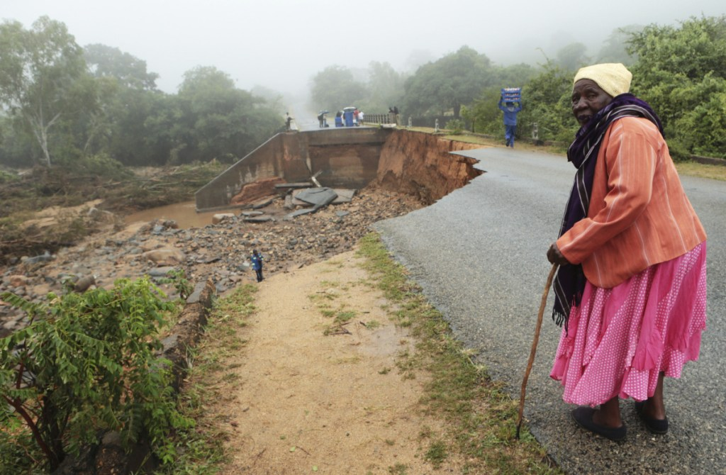 An elderly woman stands next to a collapsed bridge in Chimanimani, Zimbabwe, on Monday.