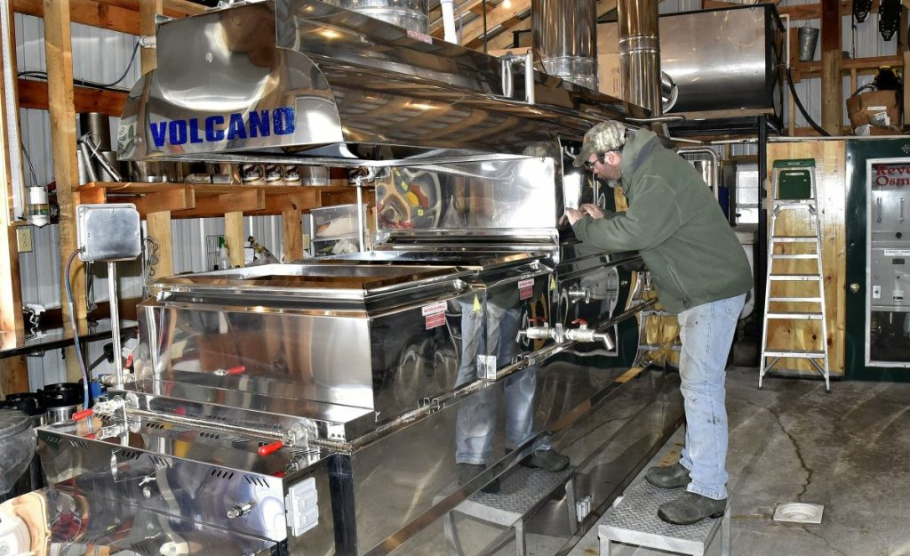 Maple syrup producer Jim Steeves peers into his evaporator Tuesday in preparation for another boil at his Smith Brothers Maple Syrup Products operation in Skowhegan. Smith said the sap was running and he made 60 gallons of syrup last Sunday. He is taking part in the annual Skowhegan Maple Fest, which begins this Friday and runs through Sunday, which is Maple Syrup Sunday.