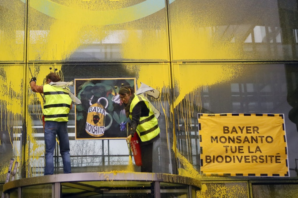 "French activists of Attac spray-paint the Paris headquarters of Bayer AG last week to protest its production of pesticides. Bayer is battling dozens of lawsuits over the weed killer Roundup, made by its American subsidiary Monsanto. ""Bayer Monsanto Kills Biodiversity,"" the placard reads."