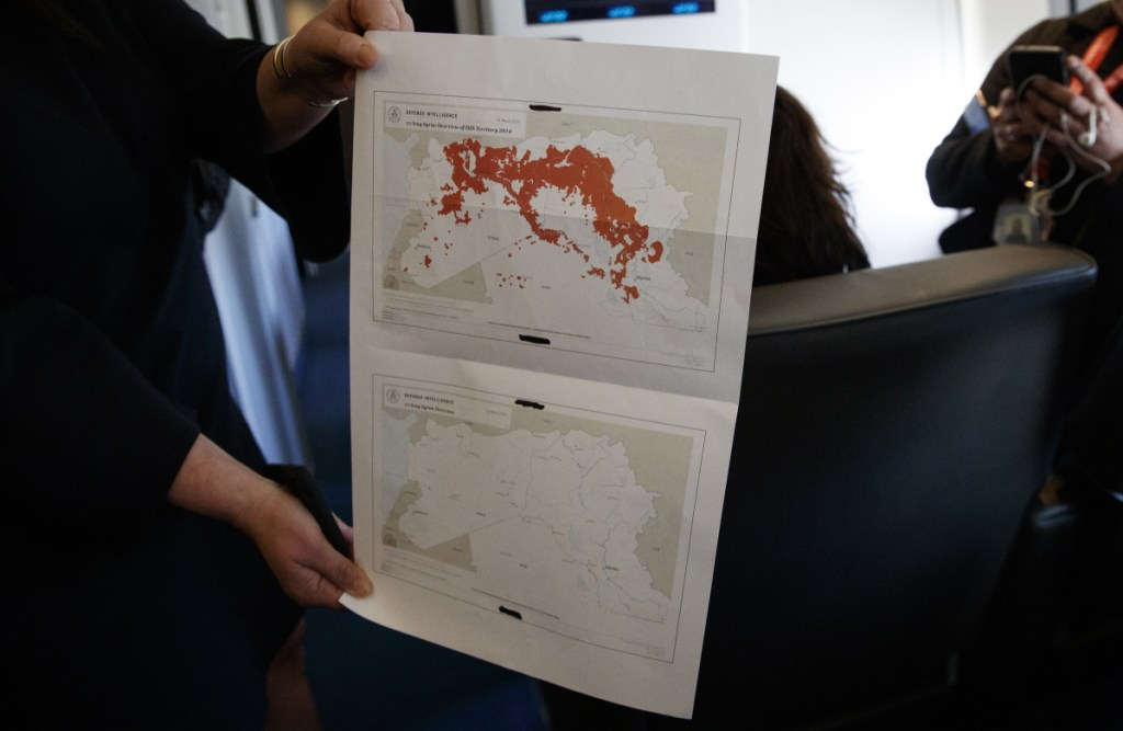 "White House press secretary Sarah Sanders holds a map of Syria in the press cabin on Air Force One on Friday after the presidential jet landed  in West Palm Beach, Fla. Sanders said the Islamic State's ""territorial caliphate has been eliminated in Syria."""