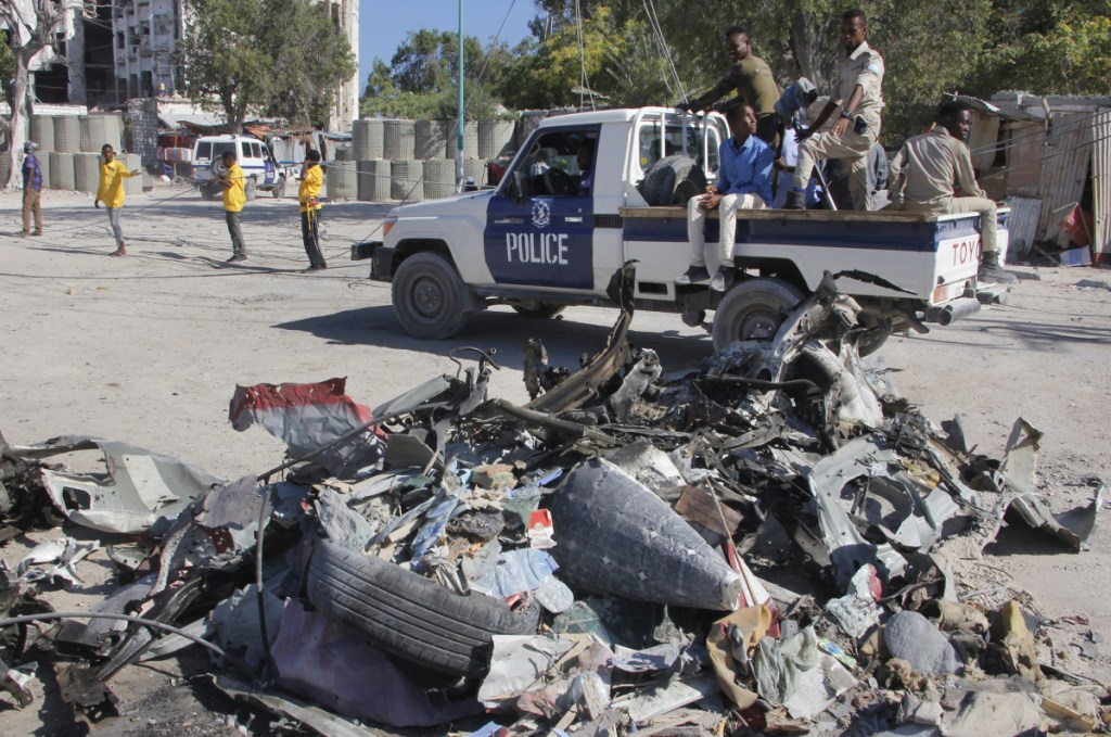 A police vehicle drives past wreckage Saturday after a suicide car bombing outside a government building in Mogadishu, Somalia. Gunmen stormed the building, killing at least five people, including the country's deputy labor minister, police said.