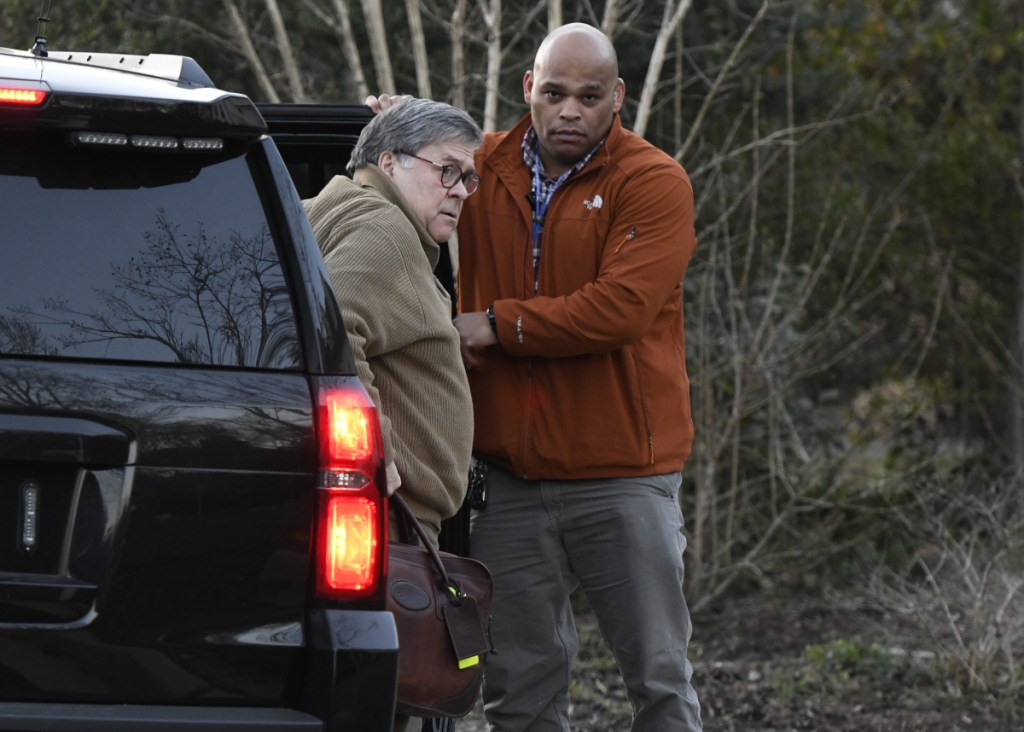 Attorney General William Barr, left, arrives home in McLean, Va., on Saturday. He and his team are poring over the Mueller report.