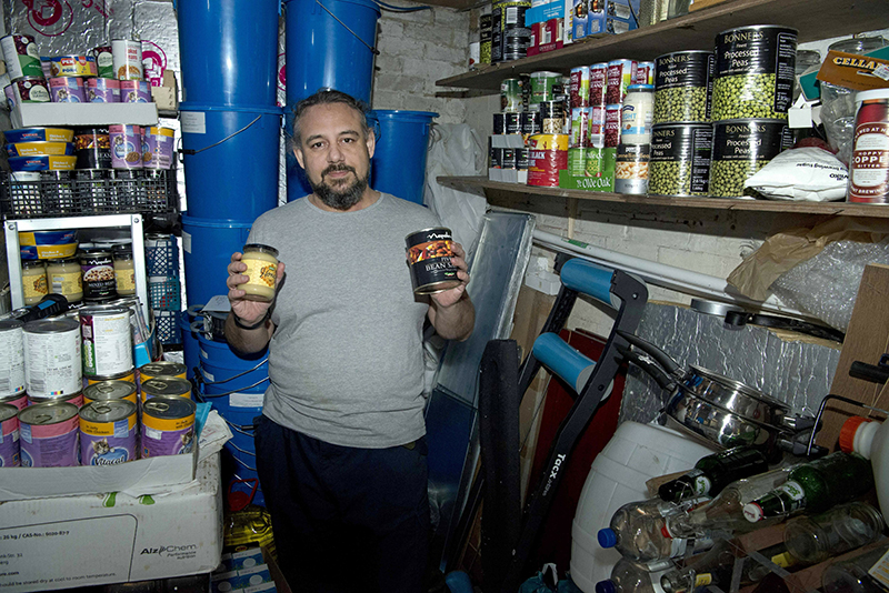 Melvin Burton holds up stored provisions in his garden shed in Littleport, Cambridgeshire, England on Friday.