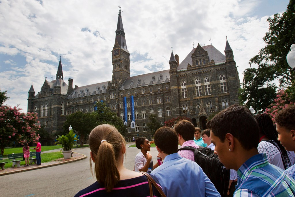Prospective students tour Georgetown University's campus in Washington in 2013. Federal authorities have charged college coaches and others in a sweeping admissions bribery case in federal court. The racketeering conspiracy charges were unsealed Tuesday against the coaches at schools including Georgetown, Wake Forest University and the University of Southern California. Authorities say the coaches accepted bribes in exchange for admitting students as athletes, regardless of their ability.