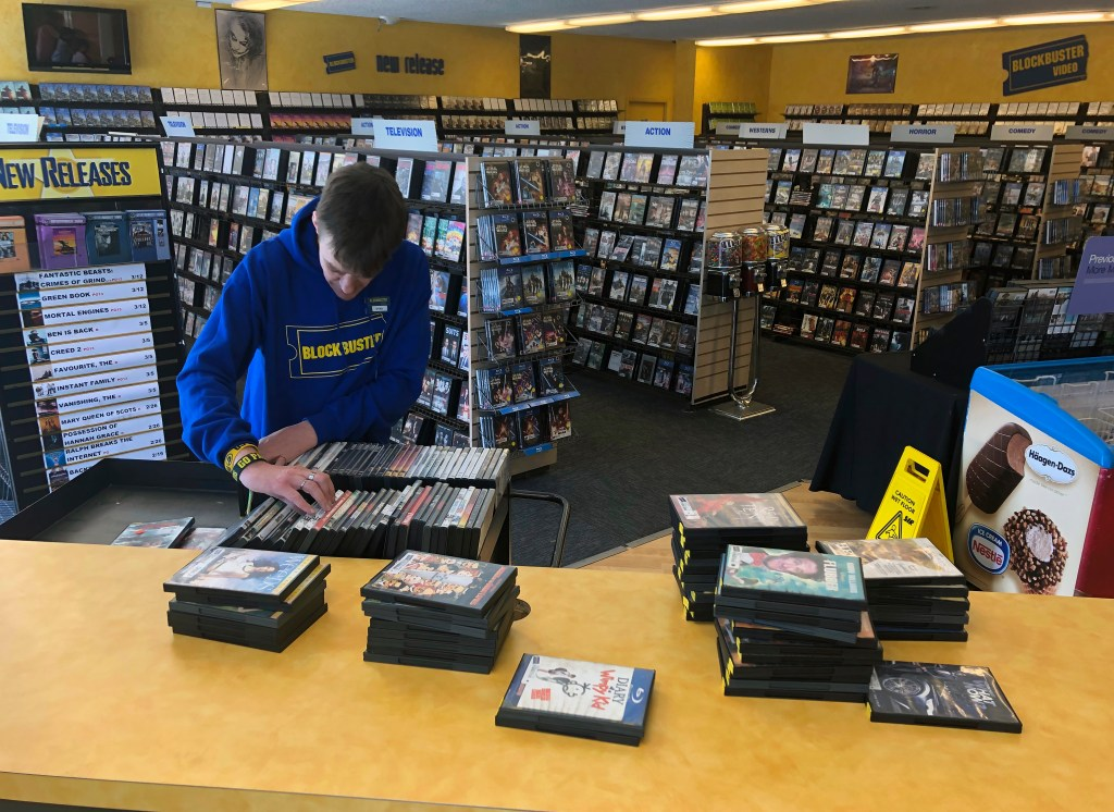 Employee Ryan Larrew alphabetizes returned movies before re-shelving them at the last Blockbuster store on the planet in Bend, Ore., on Tuesday, March 12, 2019. When a Blockbuster in Perth, Australia, shuts its doors for the last time on March 31, the store in Bend, Ore., will be the only one left on Earth, and most likely in the universe.