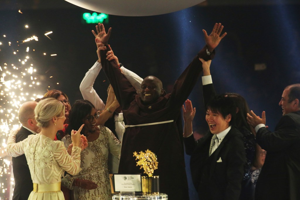 Kenyan teacher Peter Tabichi, center, reacts after winning the $1 million Global Teacher Prize in Dubai, United Arab Emirates on Sunday