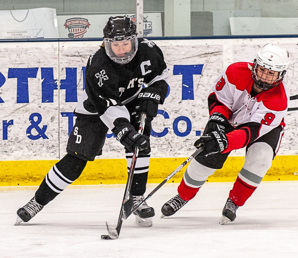 Saint Dominic Academy's Avery Lutrzykowski, left, and Red Hornets' Taylor Cailler battle for the puck earlier this month in Auburn.