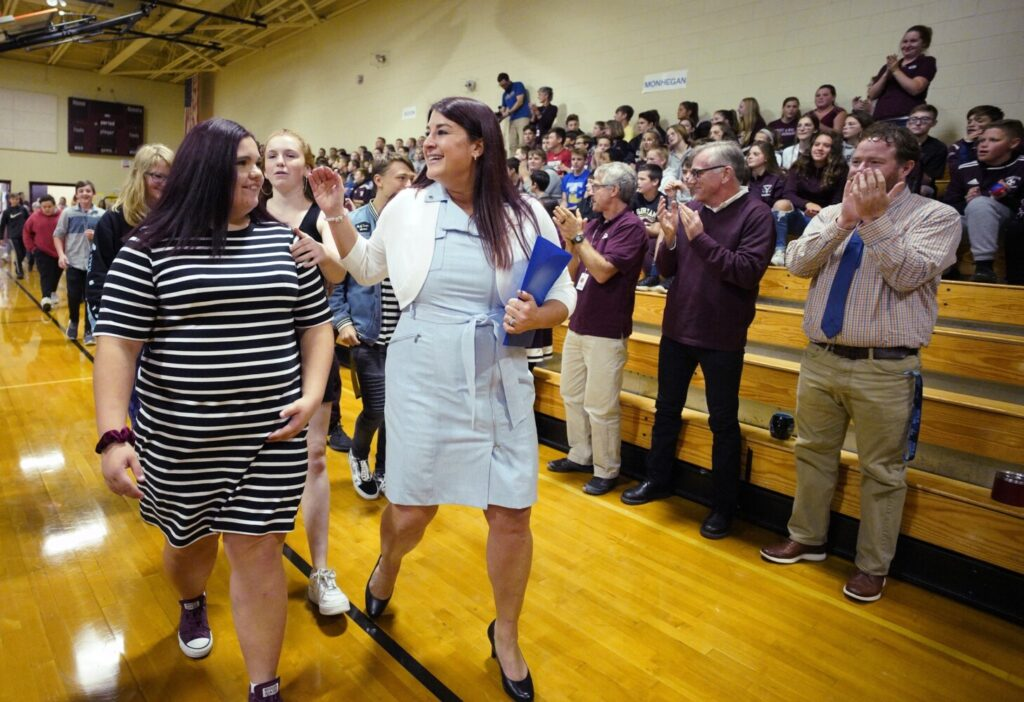 Heather Whitaker, an alternative education teacher at Gorham Middle School, walks into the school's gynmasium with Sydnie Adams, left, and other students at the start of a ceremony where she was named the 2020 Maine Teacher of the Year on Thursday.