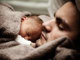 Ojciec i dziecko śpią przytuleni