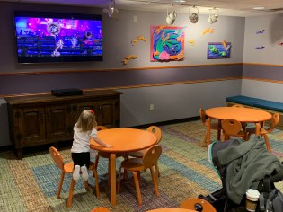 Laney watching Coco in the large kids area. Bench seating around the room for adults and plenty of room for strollers.