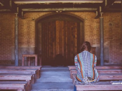 Woman praying alone in a church