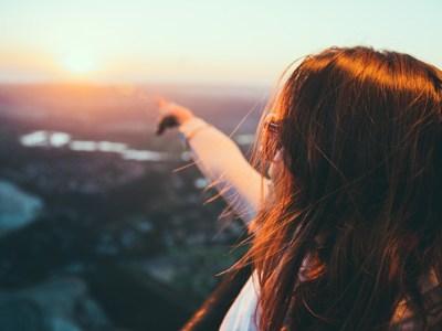 woman pointing toward horizon with sunset