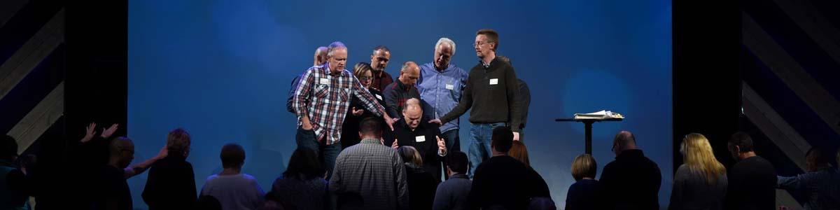 Leadership praying over new church planters