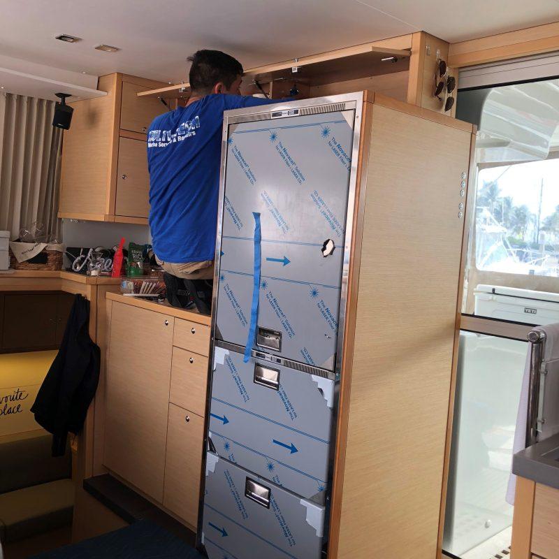 Multitech Technician Installing Refrigerator in Lagoon Catamaran