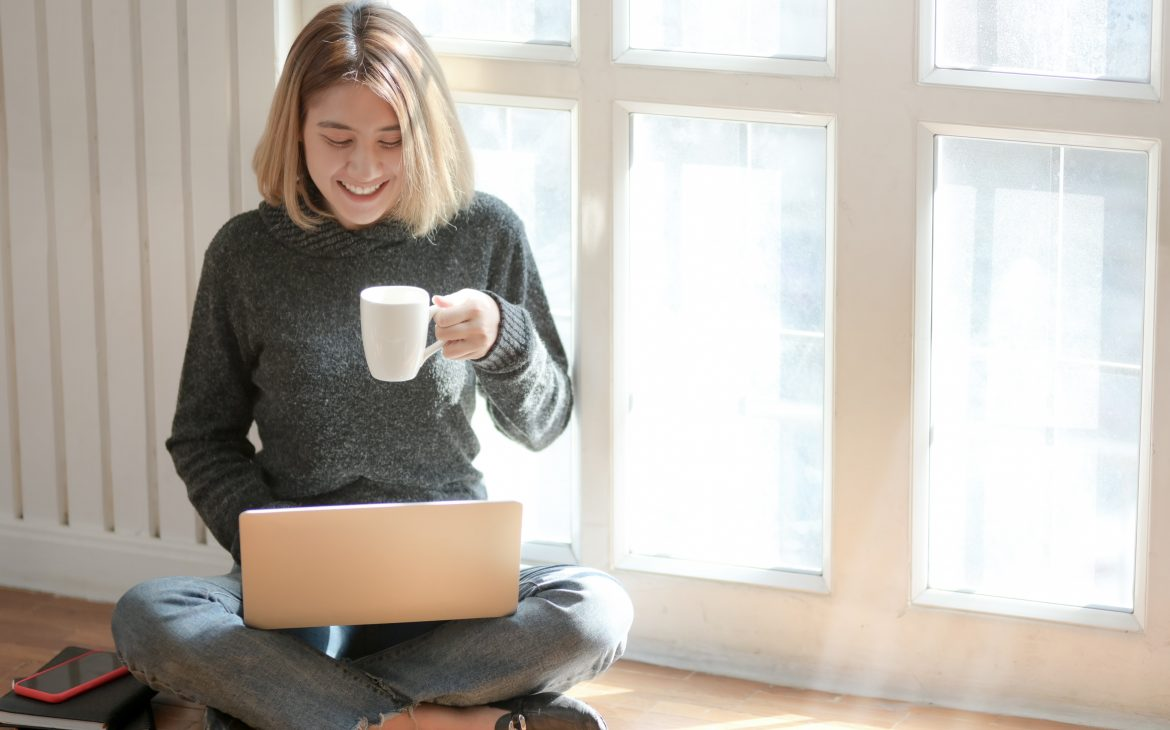 woman in grey sweater drinking coffee