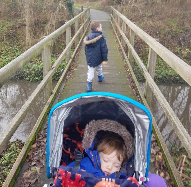 toddler-in-pram-asleep-boy-walking-over-bridge-in-country-park