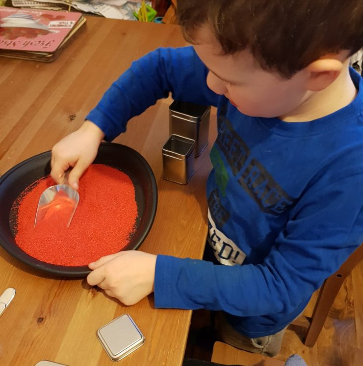 boy-playing-at-home-with-red-sand-kit