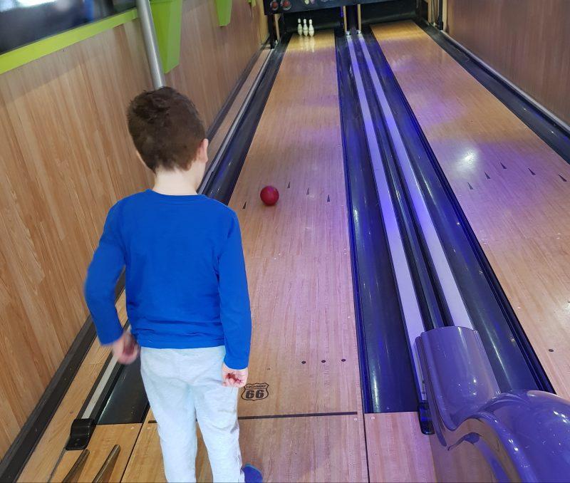 boy-watching-bowling-ball-glide-down-lane-towards-pins