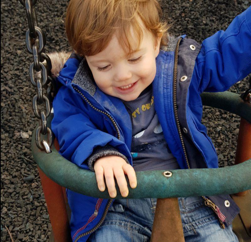 toddler-on-swing-smiling