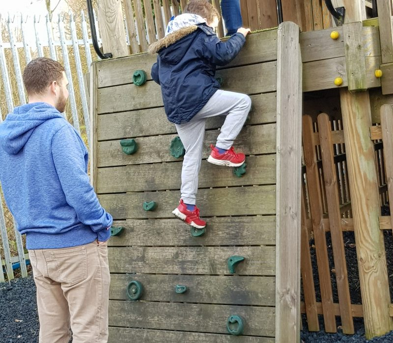 boy-climbing-climbing-wall-watched-by-his-dad