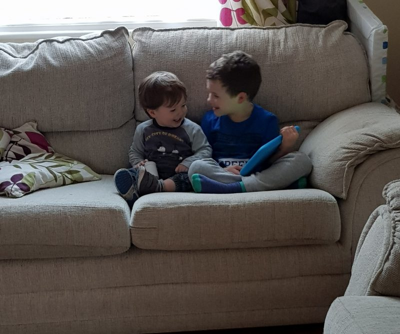 brothers-sitting-on-sofa-together-wit-a-tablet