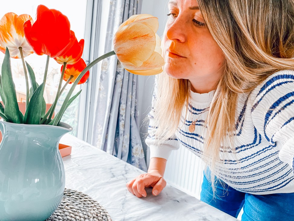 A person sitting at a table with flowers in a vase  Description automatically generated with low confidence