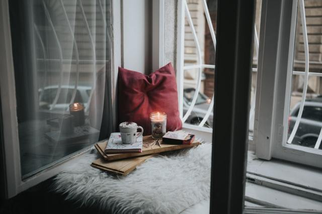 create a cosy window seat to be the envy of your frineds. this is a picture of a  cushion on a windowsill with a cuppa and a candle