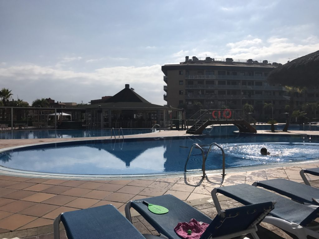 the pool and pool bar during the day. The pool is empty except for one lone swimmer
