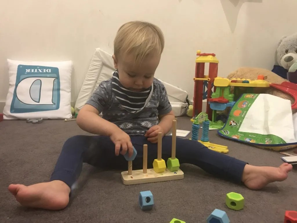 20 month milestones: dexter playing with a hape toy which involves putting blocks onto sticks