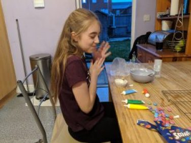 Girl sitting at a kitchen table decorating cupcakes