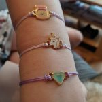 A girls arm showing three of the lucky fortune bracelets