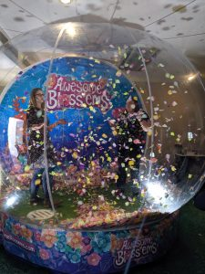 Two ladies inside an inflatable globe trying to catch a golden petal at my first blog event