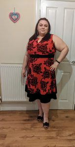 Me wearing a red dress with black flower pattern