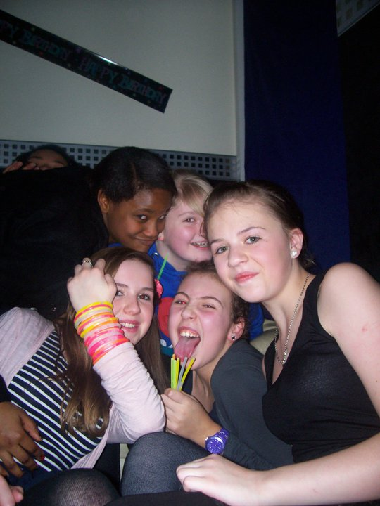 Five early teens squashed together for a photo at a party