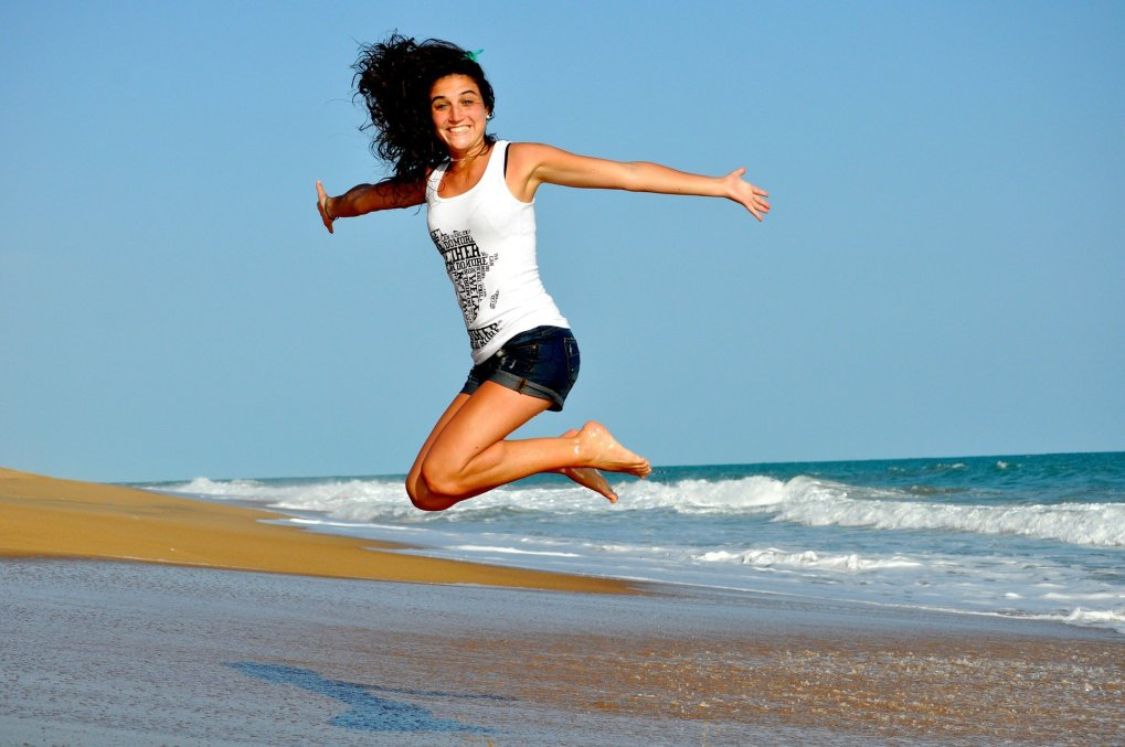 Lady at the beach jumping in the air and looking really happy