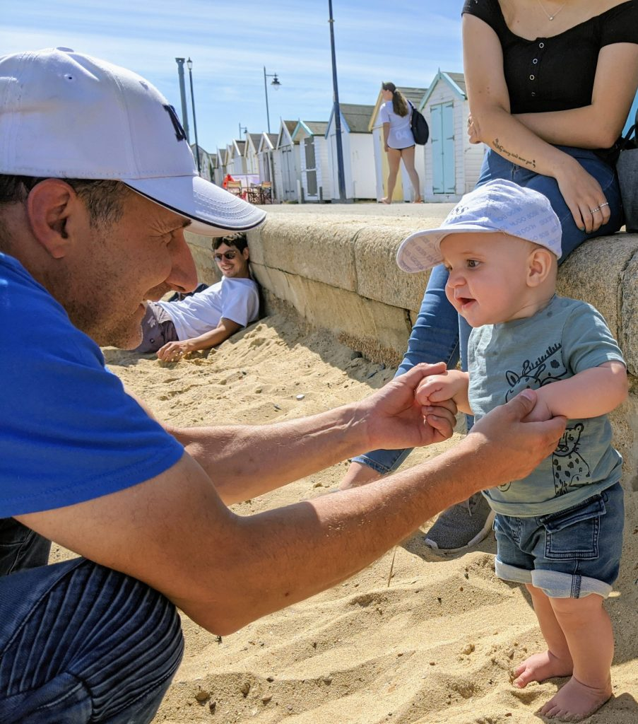 Grandad and grandson taking first steps on the beach