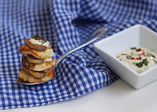 Grilled Halloumi balanced on a spoon resting next to a herb dip